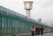Workers at the perimeter fence of what is officially known as a vocational skills education centre in Xinjiang. Photograph: Thomas Peter/Reuters